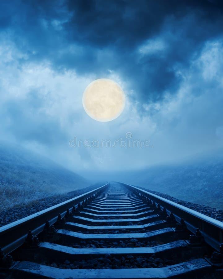 Spoorweg in nacht onder maan stock foto