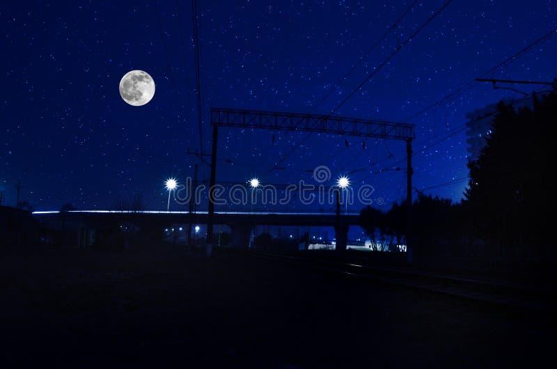 Spoorweg in nacht onder volle maan Mooi nachtlandschap met brug over de spoorweg royalty-vrije stock foto