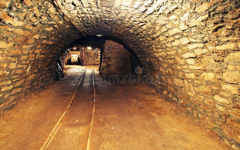 Spoorweg van de mijn de gouden ondergrondse tunnel stock afbeeldingen