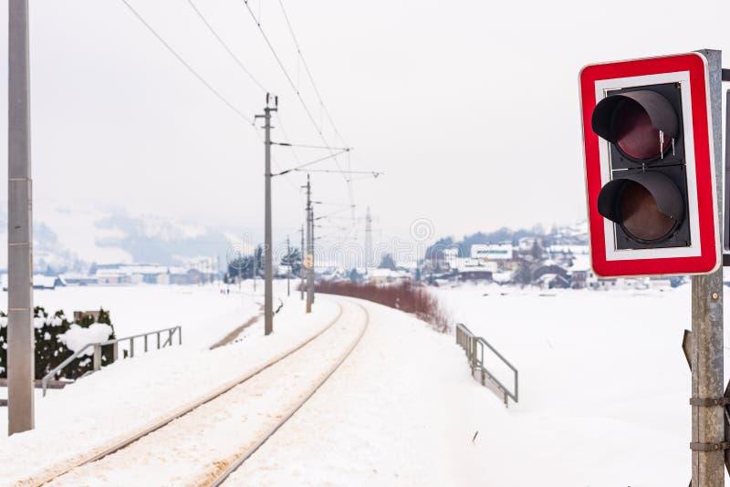 Spoorweg-weg kruising en de snow-covered gebieden in een toneellandschap van de de winterberg, Dachstein-massief, Liezen-District stock fotografie