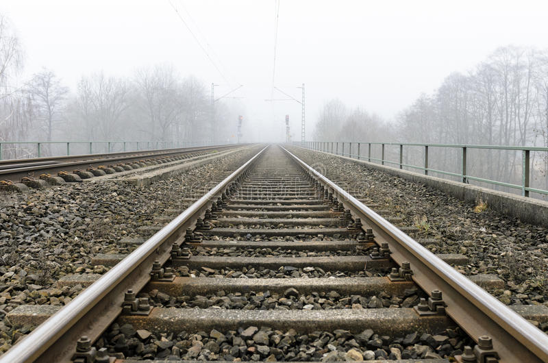 Spoorwegen die tot de wazige horizon leiden stock fotografie