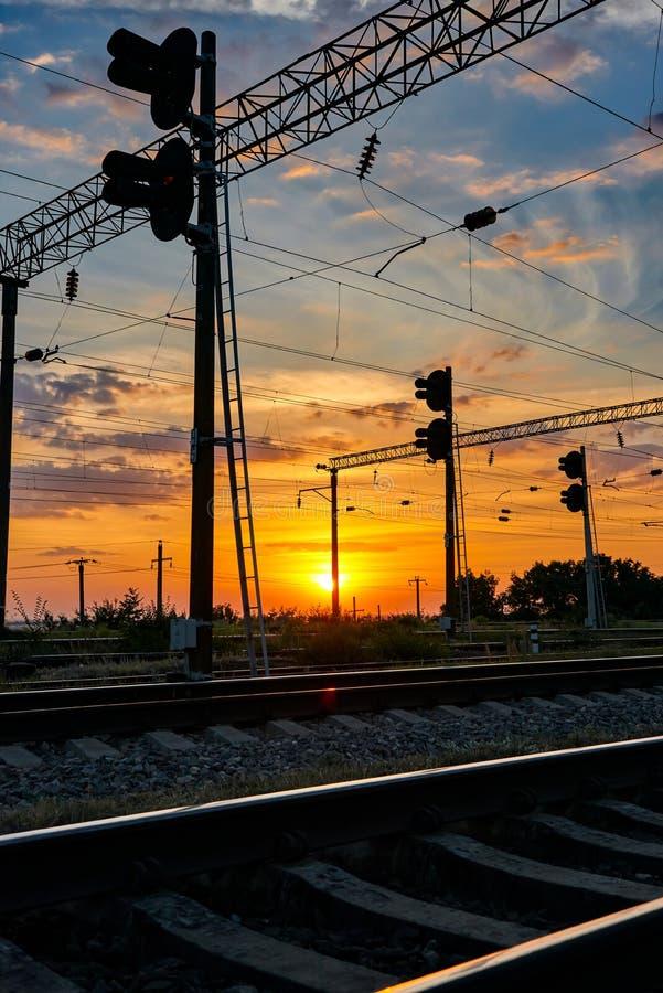 Spoorweginfrastructuur tijdens mooie zonsondergang en kleurrijke hemel, railcar en verkeerslichten, vervoer en industriële concep royalty-vrije stock fotografie