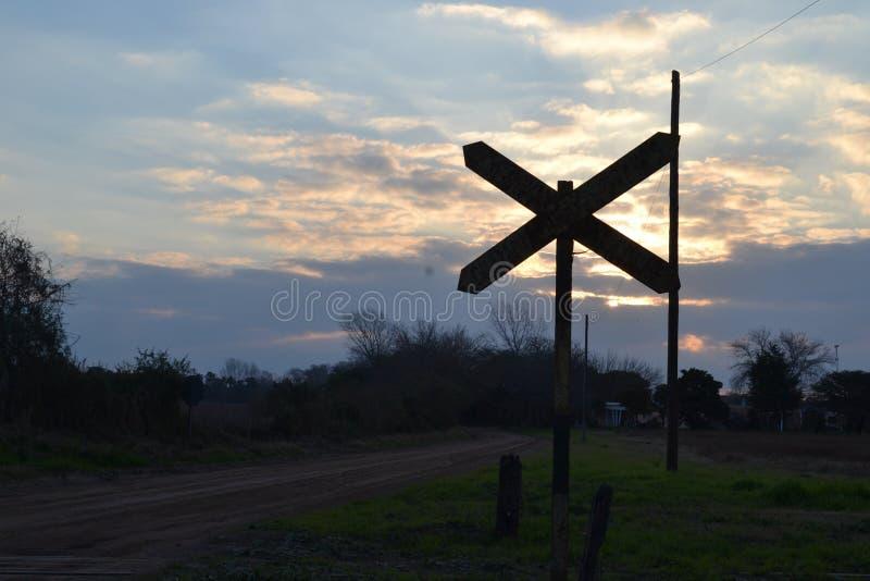 Spoorwegsignaal in tegenstelling tot zonsondergang en het verdonkeren van een semi-bewolkte hemel en een straat van het land stock foto