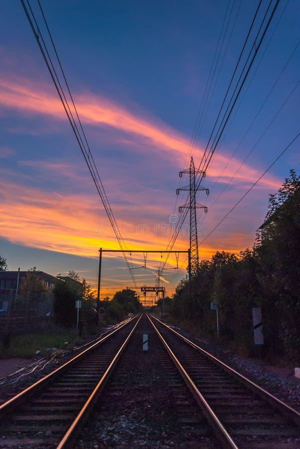 Spoorwegspoor die op de laatste zonstralen van de dag wijzen stock foto