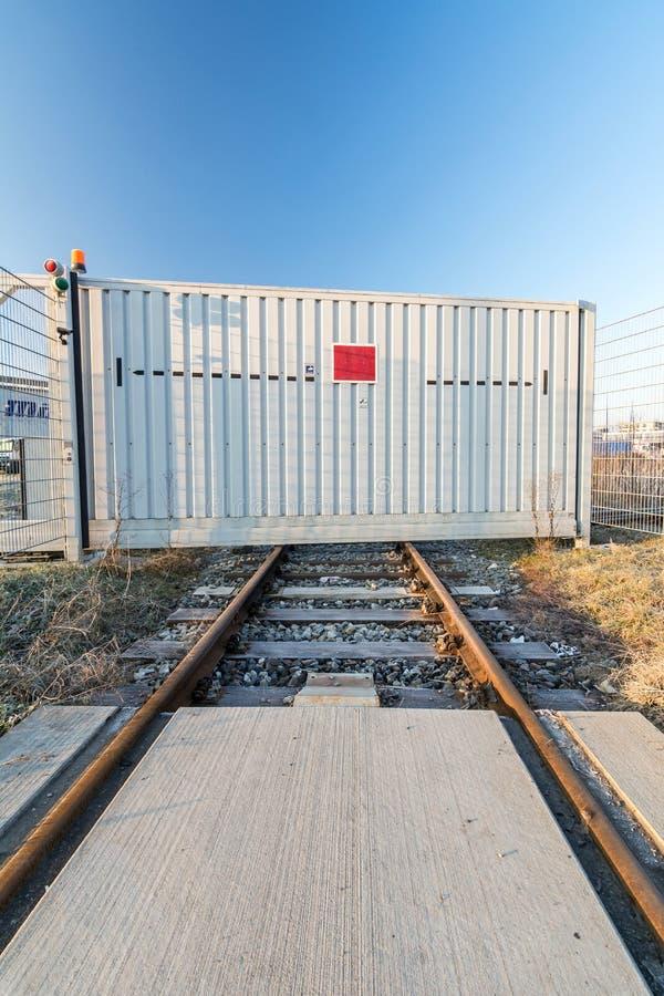 Spoorwegsporen die bij gesloten poort van commercieel gebied beëindigen stock afbeeldingen