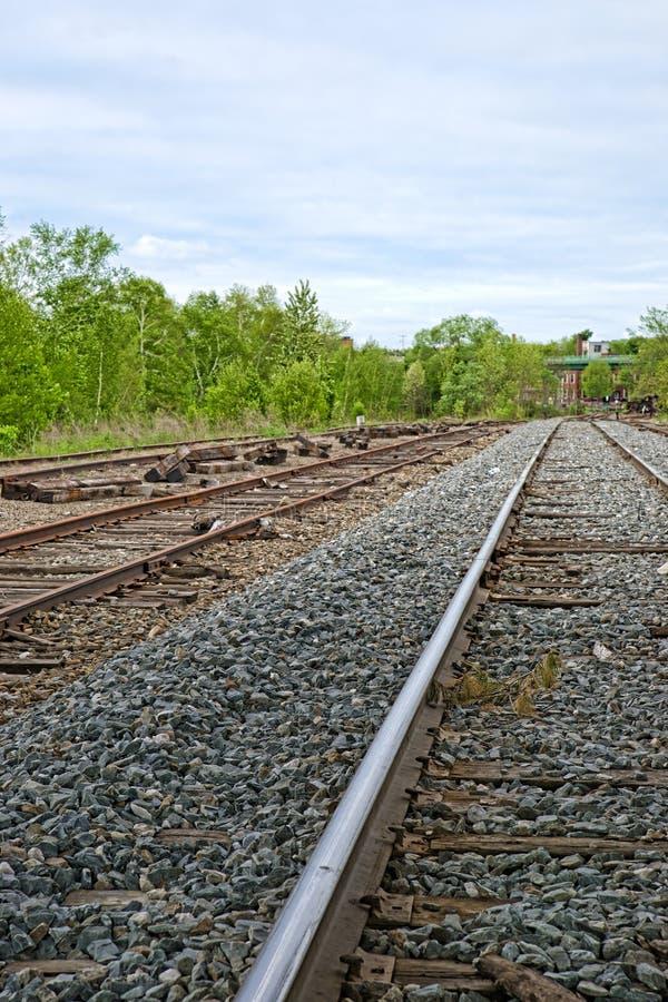 Spoorwegsporen die in stad leiden stock afbeeldingen