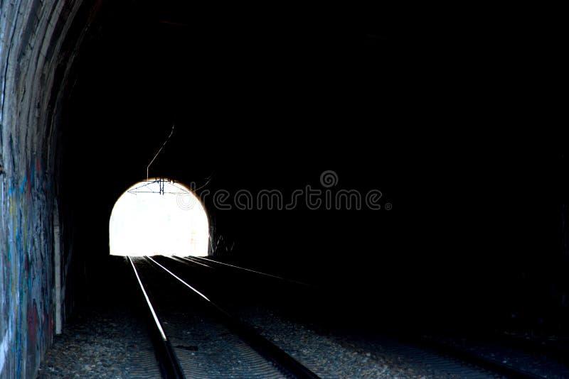 Spoorwegtunnel op dubbel spoor Spoorweginfrastructuur Licht aan het eind van de tunnel Oude die steentunnel met graffity wordt ge royalty-vrije stock afbeeldingen