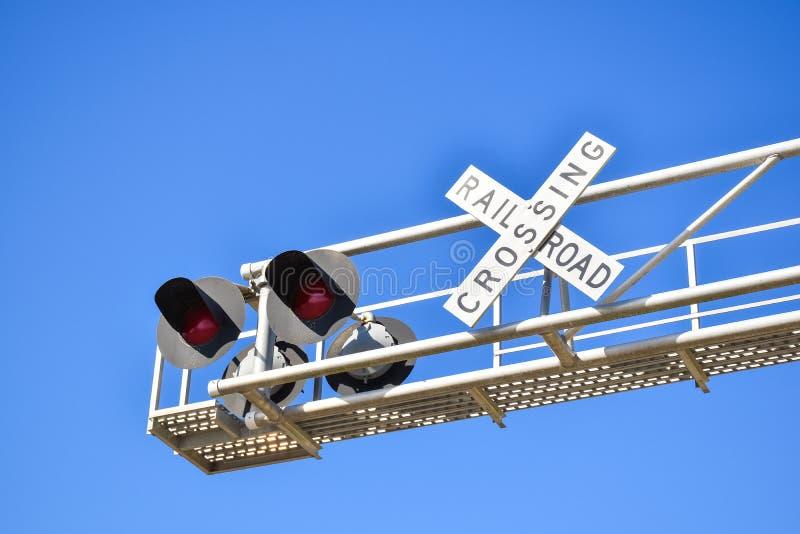 Spoorwegwaarschuwing die teken kruisen onder duidelijke blauwe hemel stock afbeelding