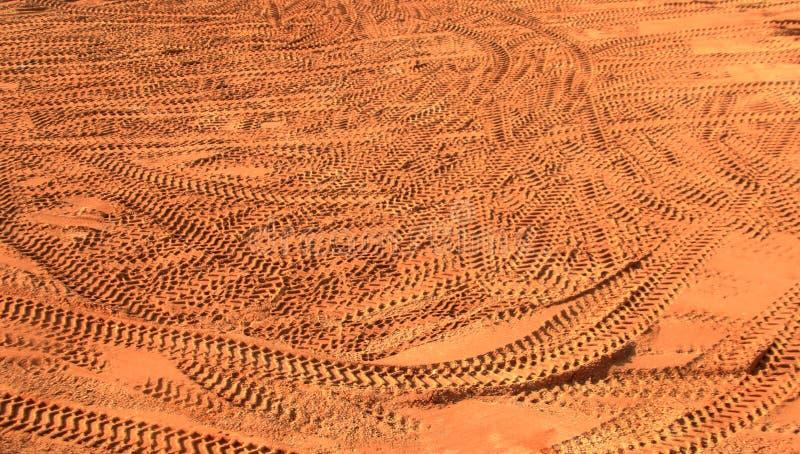 Sporen van banden in de zandbodem - bruine achtergrond stock foto