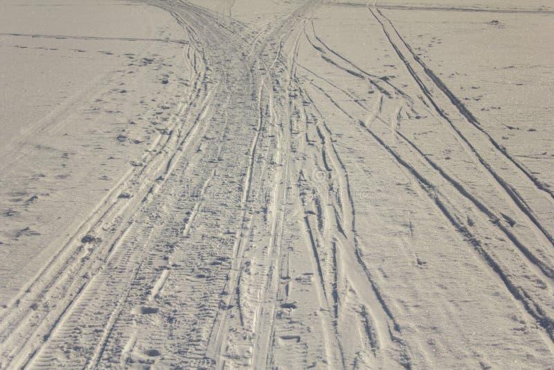 Sporen van ski en sneeuwscooter op de witte sneeuw stock afbeelding