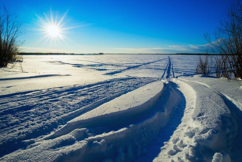 Sporen van sneeuwscooters op de sneeuw op gebied stock afbeeldingen