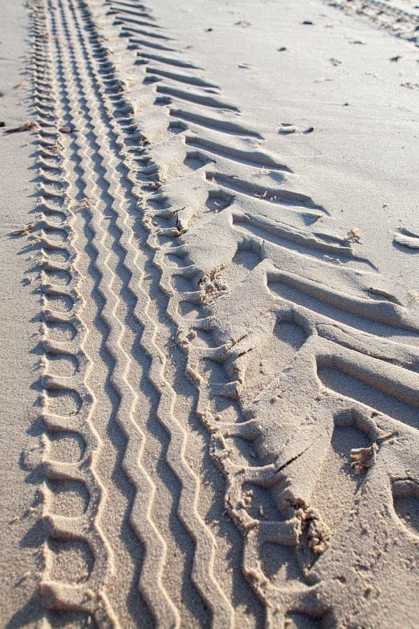 Sporen in zand Het loopvlakafdruk van de tractorband op strand royalty-vrije stock foto