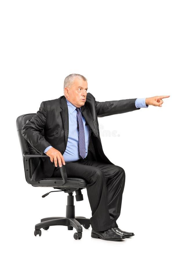 Sporgenza arrabbiata che si siede nella poltrona e nell'indicare fotografie stock libere da diritti