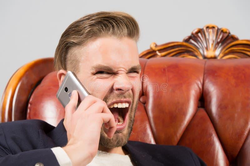 Sporgenza arrabbiata Dell'uomo di grido fondo ben curato di grey del telefono cellulare aggressivamente Telefono cellulare arrabb immagini stock