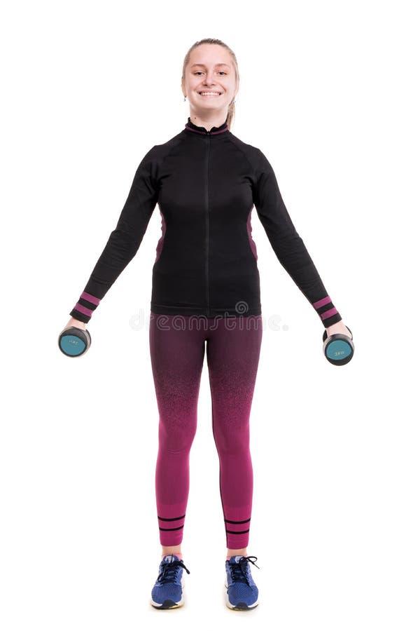 Sportów i opieki zdrowotnej pojęcie Uśmiechnięta nastoletnia dziewczyna w sportswear opracowywa z dumbbells w studiu zdjęcia stock