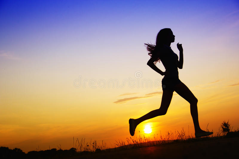 Sport. Black silhouette of a jogging woman at sunset. sport