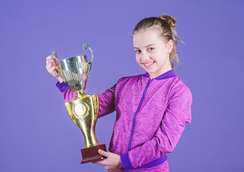 Sport achievement. Celebrate victory. Girl hold golden goblet. Importance of capturing evidence of kids progress. Proud. Of her achievement. Celebrating royalty free stock photo
