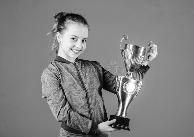 Sport achievement. Celebrate victory. Girl hold golden goblet. Importance of capturing evidence of kids progress. Proud. Of her achievement. Celebrating royalty free stock photos