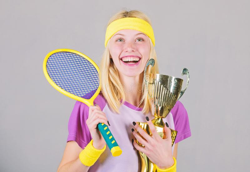 Sport achievement. Celebrate victory. Tennis champion. Athletic girl hold tennis racket and golden goblet. Win tennis. Game. Tennis player win championship royalty free stock photos