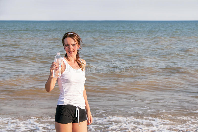 Sport active woman drinking water after exercising stock photos