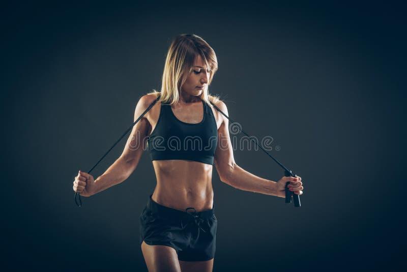 Sport, activiteit Leuke vrouw met touwtjespringen Spiermeisjesbl stock fotografie