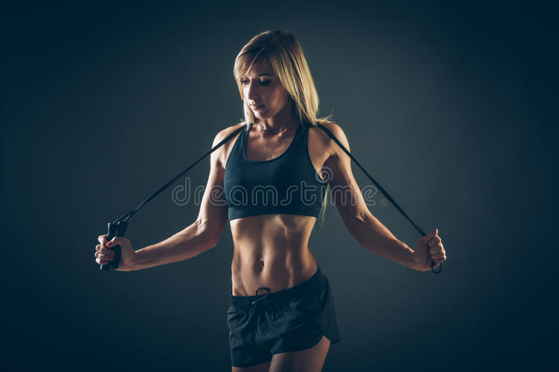 Sport, activity. Cute woman with skipping rope. Muscular woman black background stock photos