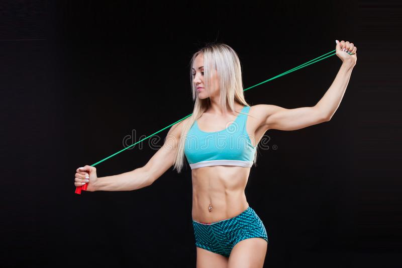 Sport, activity. Cute woman with skipping rope. Muscular woman black background. royalty free stock photography