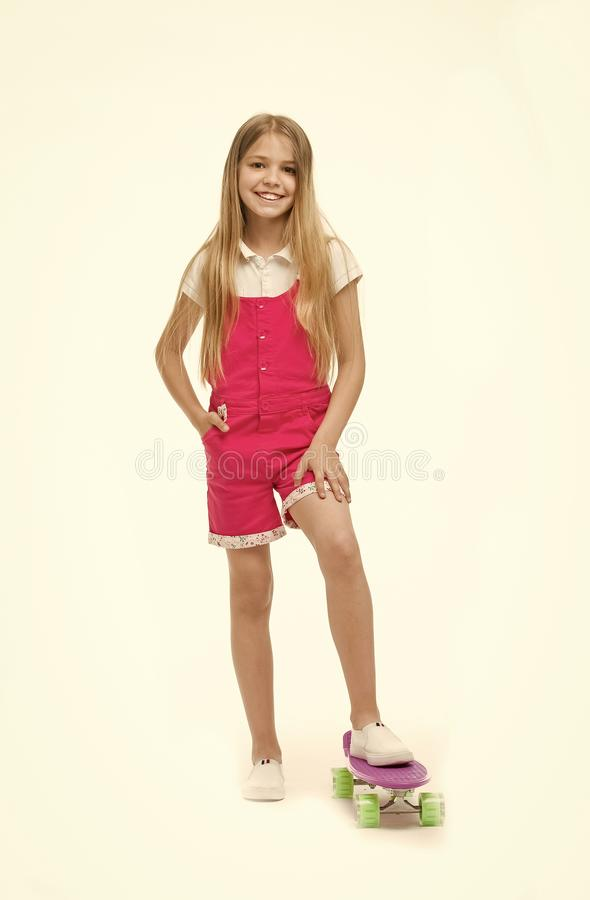 Sport activity and energy. Small girl smile with skate board isolated on white. Child skater smiling with longboard. Skateboard kid in pink jumpsuit. Childhood stock images