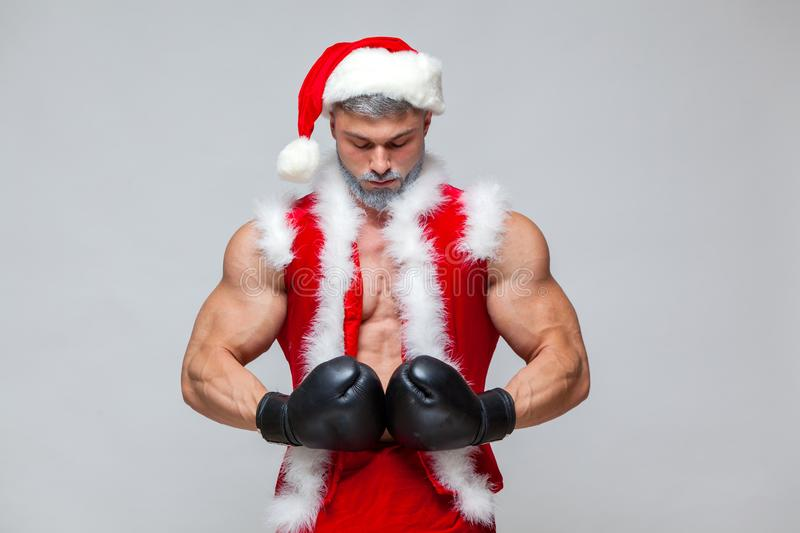 Sport, activity. Santa Claus with boxing glove. Young muscular man wearing Santa Claus hat demonstrate his muscles. On a homogeneous gray background stock photo