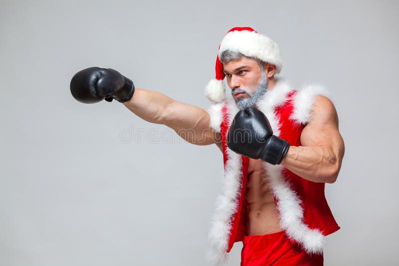 Sport, activity. Santa Claus with boxing glove. Young muscular man wearing Santa Claus hat demonstrate his muscles. On a homogeneous gray background royalty free stock photography