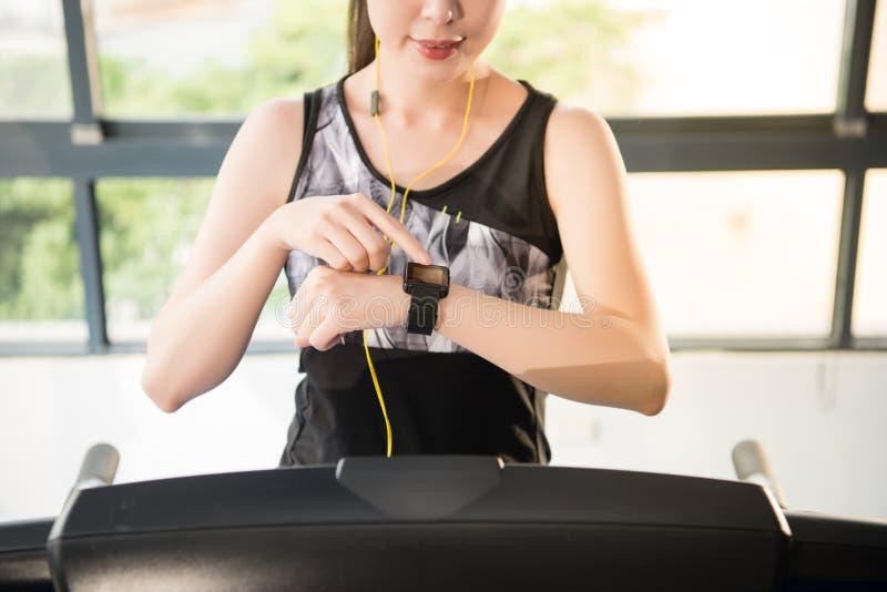 Sport asian woman running treadmill. smartwatch to listening mus royalty free stock image