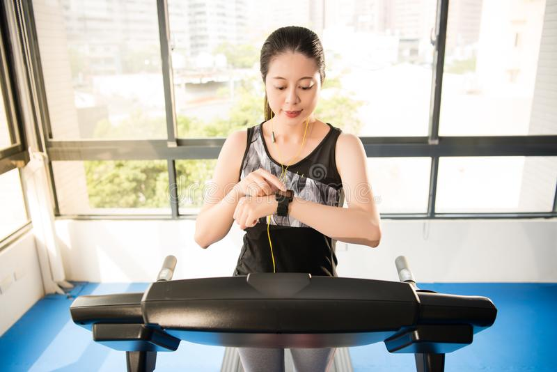 Sport asian woman running treadmill. smartwatch to listening mus royalty free stock images