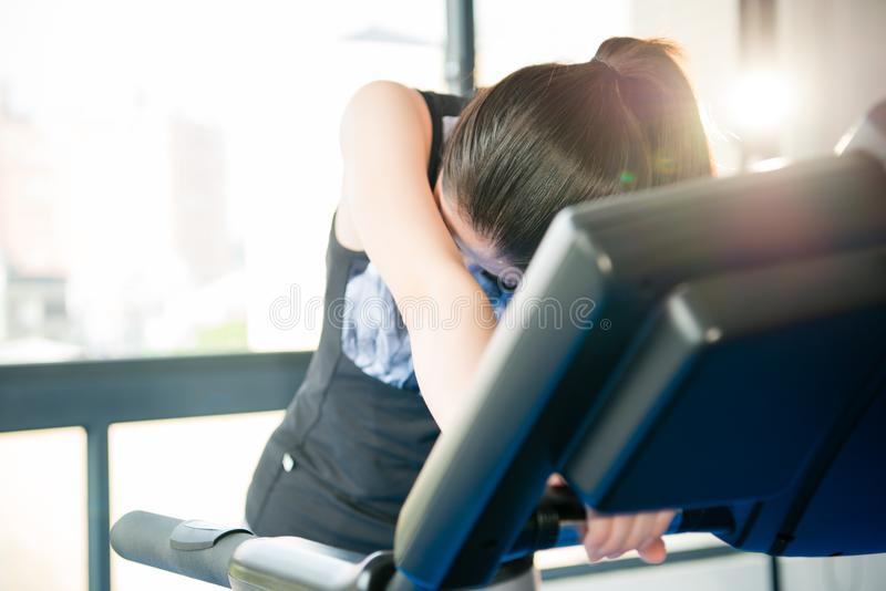 Sport asian woman running treadmill sweat and feel tired. Take rest. indoors gym background. health sport concept royalty free stock image