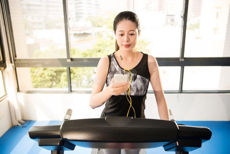 Sport asian woman running treadmill use smartphone listening mus stock photo