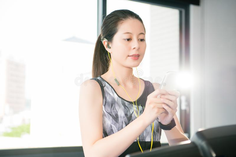 Sport asian woman running treadmill use smartphone listening mus. Sport asian woman running treadmill use smartwatch and smartphone listening music. indoors gym stock photo
