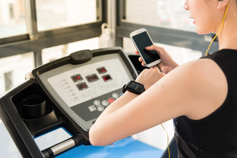 Sport asian woman use smartwatch check pulse rate listening music. Sport asian woman running treadmill use smartwatch connect smartphone listening music. indoors royalty free stock image