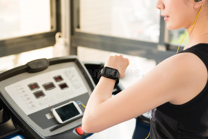 Sport asian woman use smartwatch check pulse rate listening music. Sport asian woman running treadmill use smartwatch check pulse rate listening music. indoors royalty free stock photos