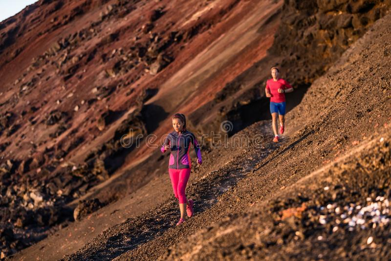 Sport athletes on trail run exercising cardio training together in summer outdoors at sunset. Afternoon couple workout running in. Mountain landscape, volcano stock photos