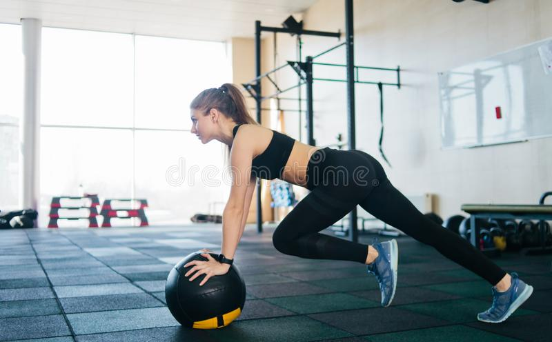 Sport. Athletic attractive woman doing an exercise lifting the leg up leaning on the medicine ball. Functional training concept royalty free stock photo