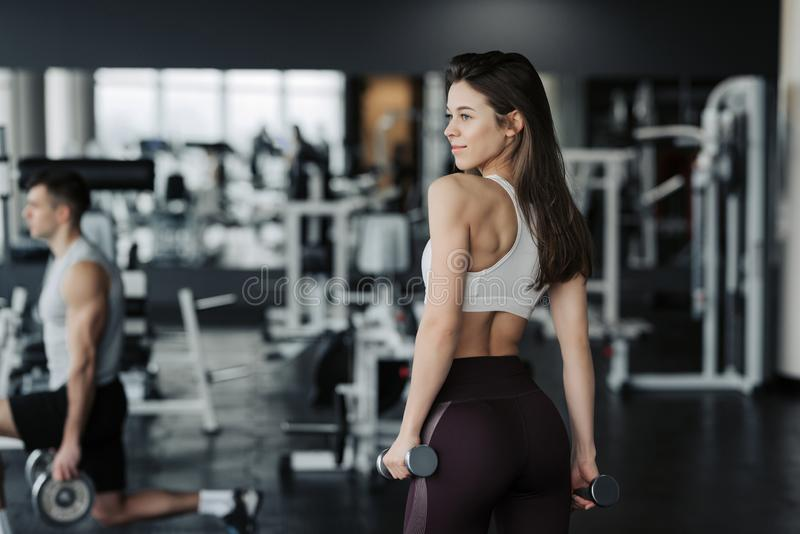 Sport. Athletic fitness woman pumping up muscles with dumbbells. Brunette sexy fitness girl in sport wear with perfect body in the stock images