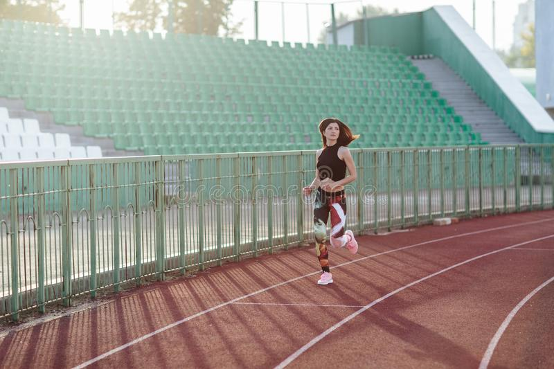 Sport. Athletic young brunette woman in pink sneakers, leggings and top run on running track stadium at sunset. her hair is. Developing. Concept run. concept of royalty free stock image