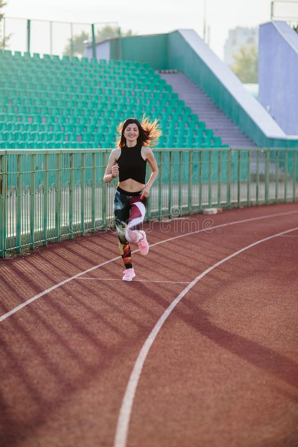Sport. Athletic young brunette woman in pink sneakers, leggings and top run on running track stadium at sunset. her hair is. Developing. Concept run. concept of stock photos