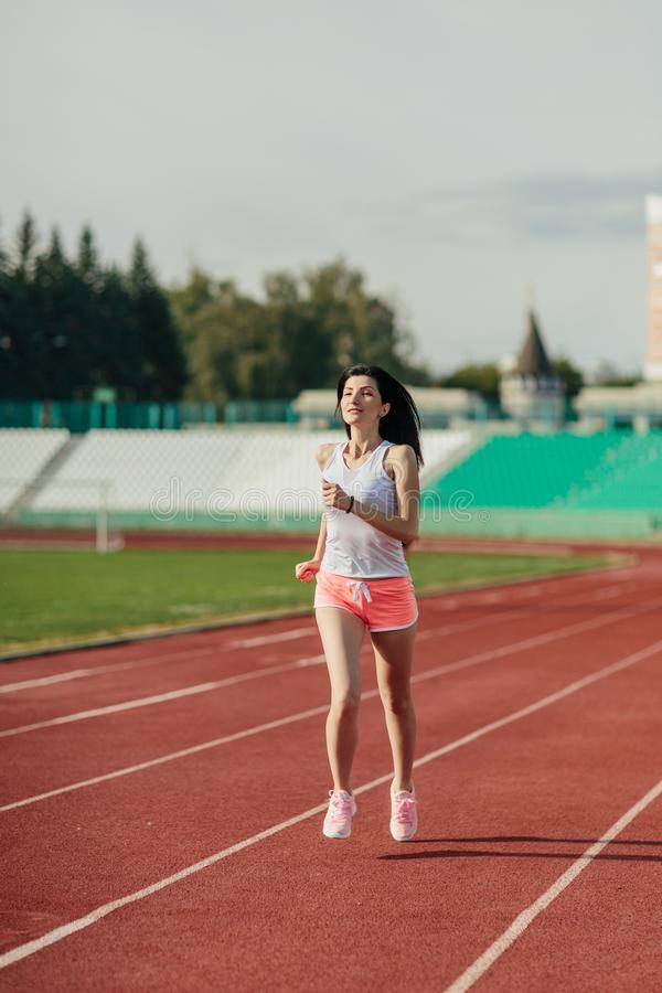 Sport. Athletic young brunette woman in pink sneakers, shorts and tops run on running track stadium at sunset. her hair is. Developing. Concept run. concept of royalty free stock photo