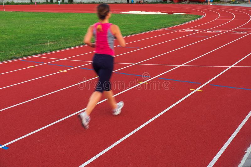 sport Athletische junge Frau in den Turnschuhen laufen auf Laufbahn lizenzfreie stockfotos