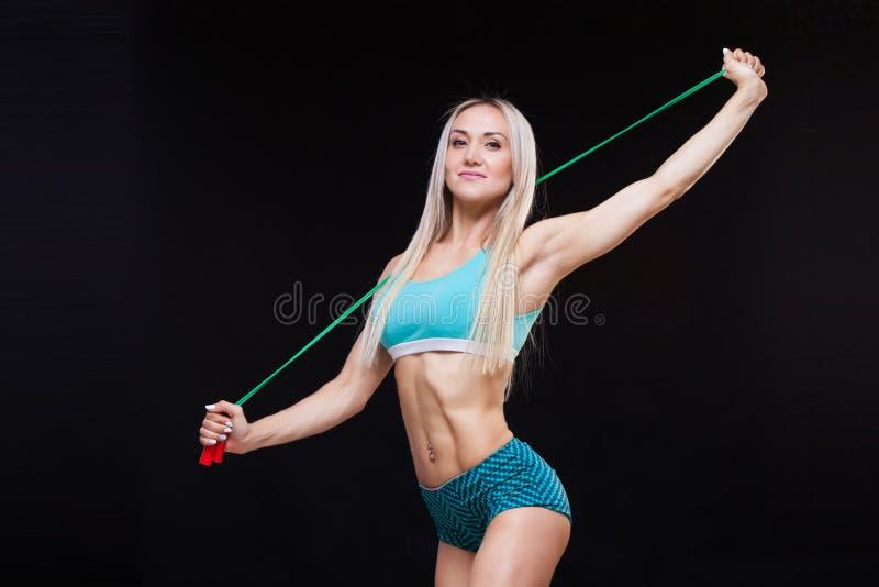 Sport, attività Donna sveglia con il salto della corda Fondo muscolare del nero della donna immagini stock