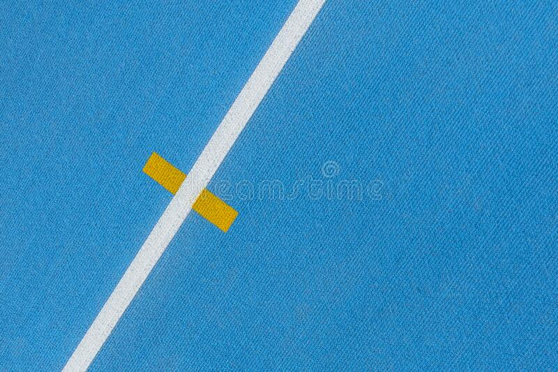 Sport background. Blue running track with white lines and yellow mark in sport stadium. Top view. Blue running track with white lines and yellow mark in sport stock photography