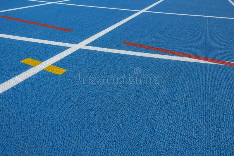 Sport background. Blue running track with white lines, yellow and red mark in sport stadium. Top view. Sport background. Blue running track with white lines stock image