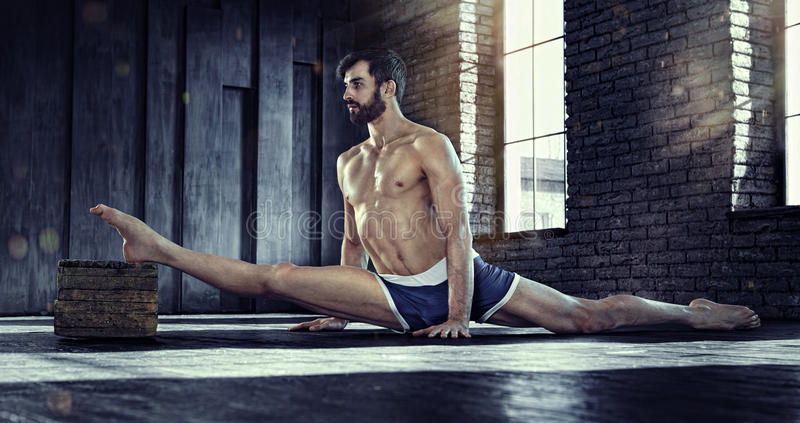 Sport backgrounds. Young athletic man doing split. stock images