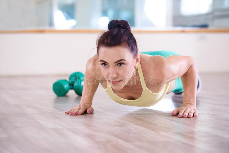 Sport. Beautiful athletic girl doing push-ups exercises in the gym stock photo