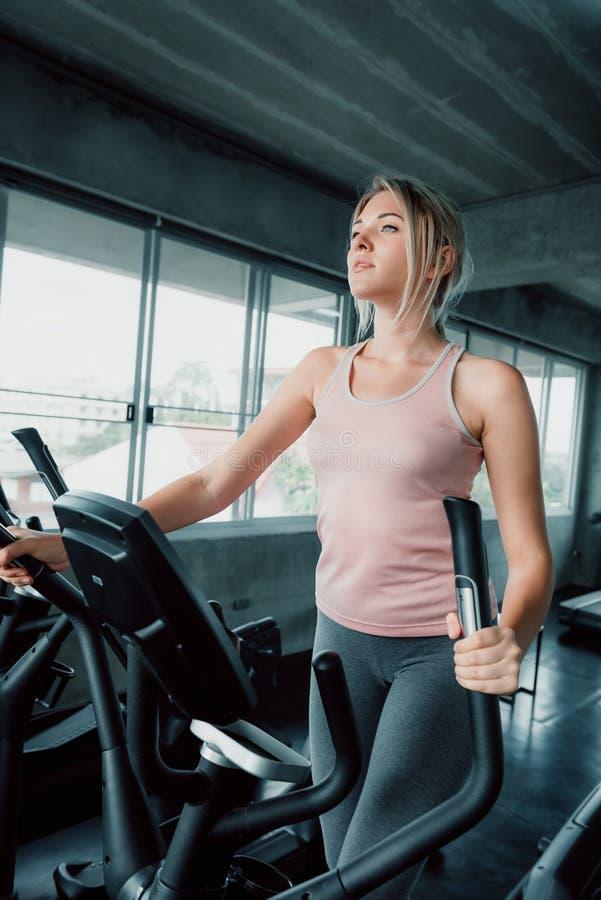 Sport Beautiful Woman Exercising Workout on Elliptical in Fitness Training Club, Pretty of Caucasian Women in Sportswear Working stock photo